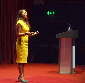 Shabnam Parkar wearing yellow dress on stage presenting at at TEDx